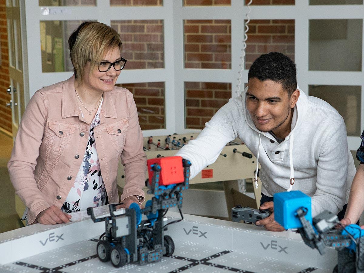 Biotalouden opiskelijat katselevat pientä robottia