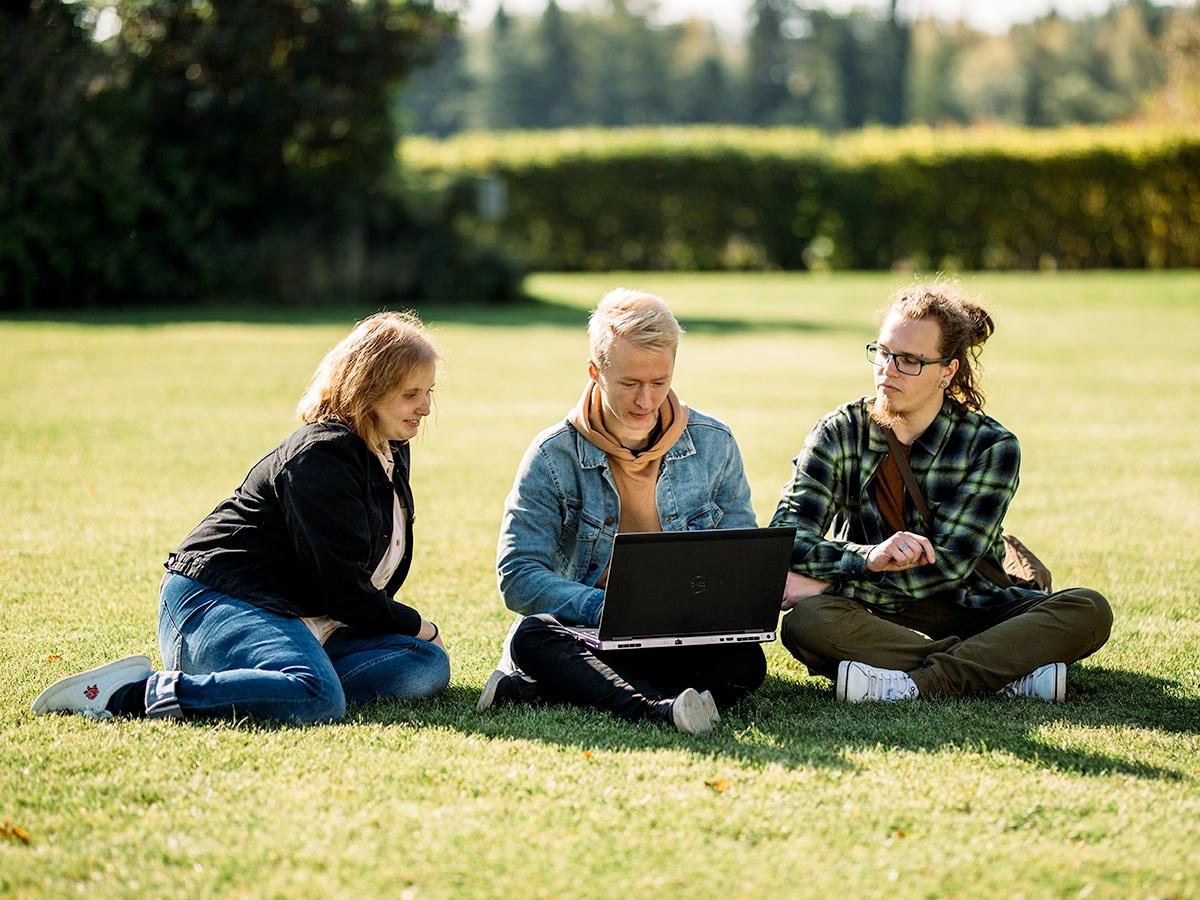 Kolme opiskelijaa kesäisellä nurmella läppärin kanssa