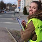 liikenneala hymyileva nainen huomioliivissa kadulla