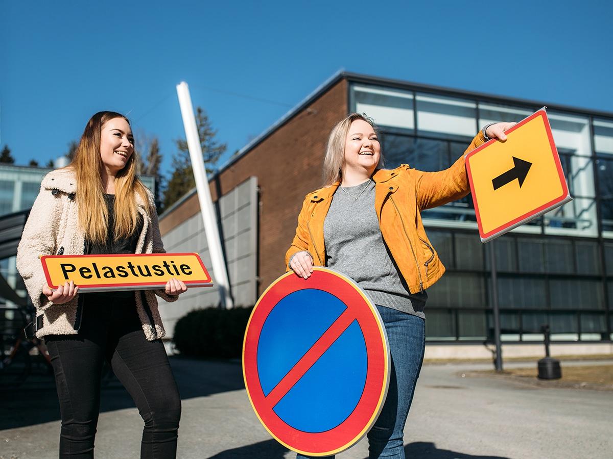 Kaksi opiskelijaa pitää opastekylttejä ja osoittaa eteenpäin