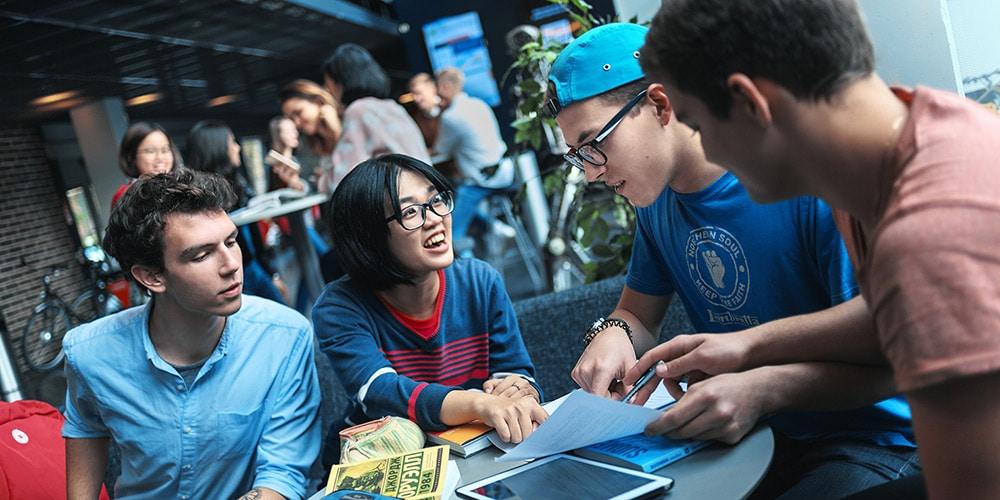 liikenneala opiskelijat tyoskentelevat poydan aaressa yhdessa