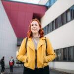keltatakkinen opiskelija Hämeenlinnan kampuksen edustalla
