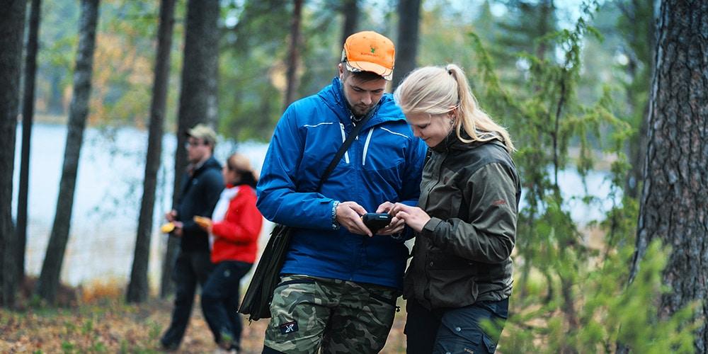 metsatalous opiskelijat puhelimella metsassa