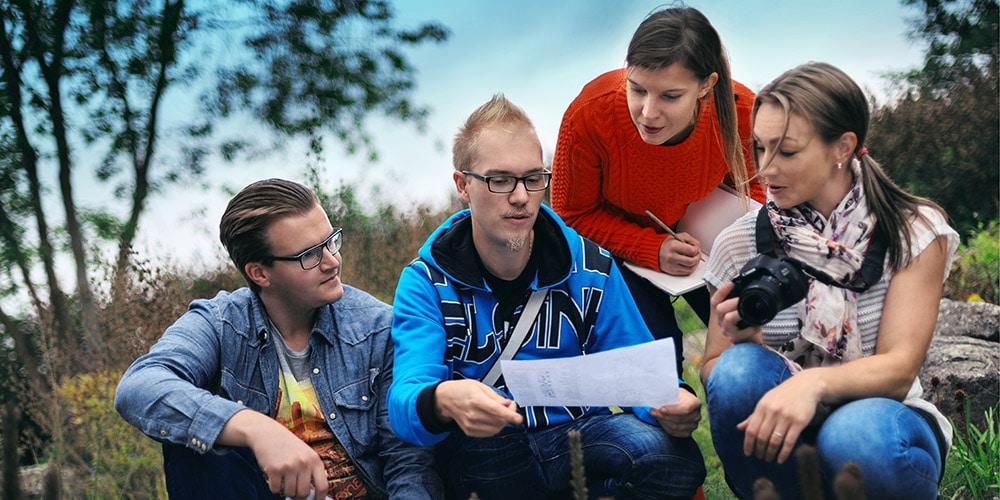 puutarhatalous opiskelijat katsovat paperia ulkona