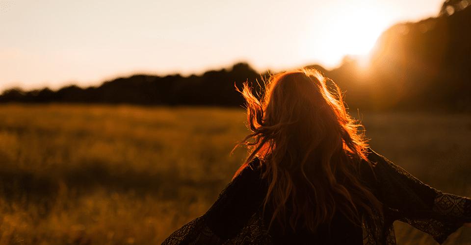 Nainen auringon laskussa pellolla