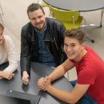 Opettaja ja kaksi opiskelijaa pöydän ympärillä