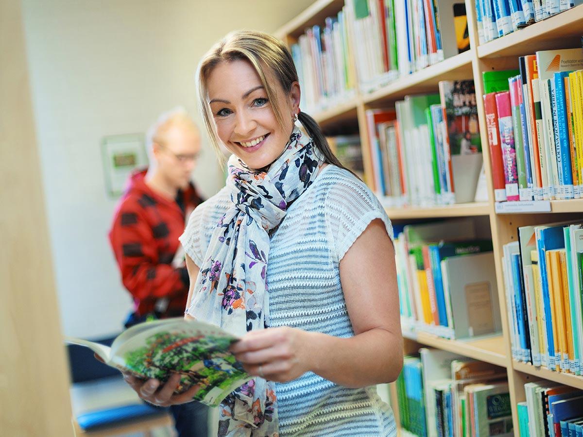 alykkaat palvelut digitaalisessa ymparistossa nainen kirjastossa kirja kadessa