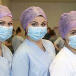 sairaanhoitajan vastaanottotoiminta kolme naista hoitajan vaatteissa ja suusuojissa