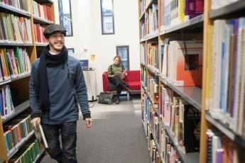 mies kavelee kirjaston hyllyjen valissa