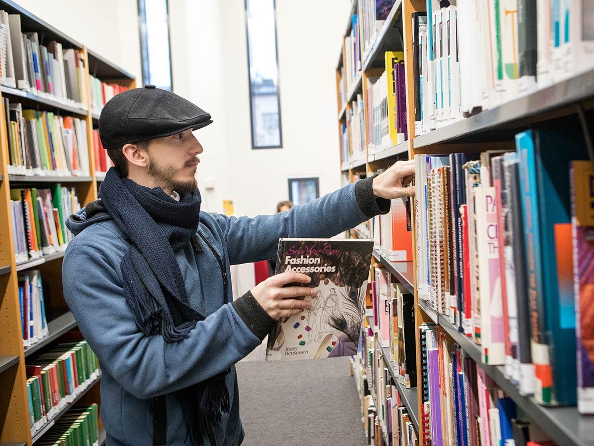 opinnaytetyot mies laittaa kirjaa kirjaston hyllyyn