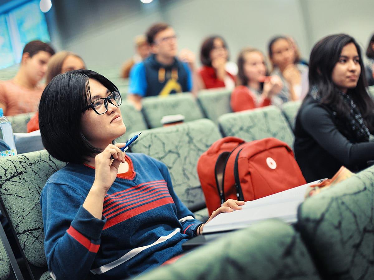 nainen istuu auditoriossa
