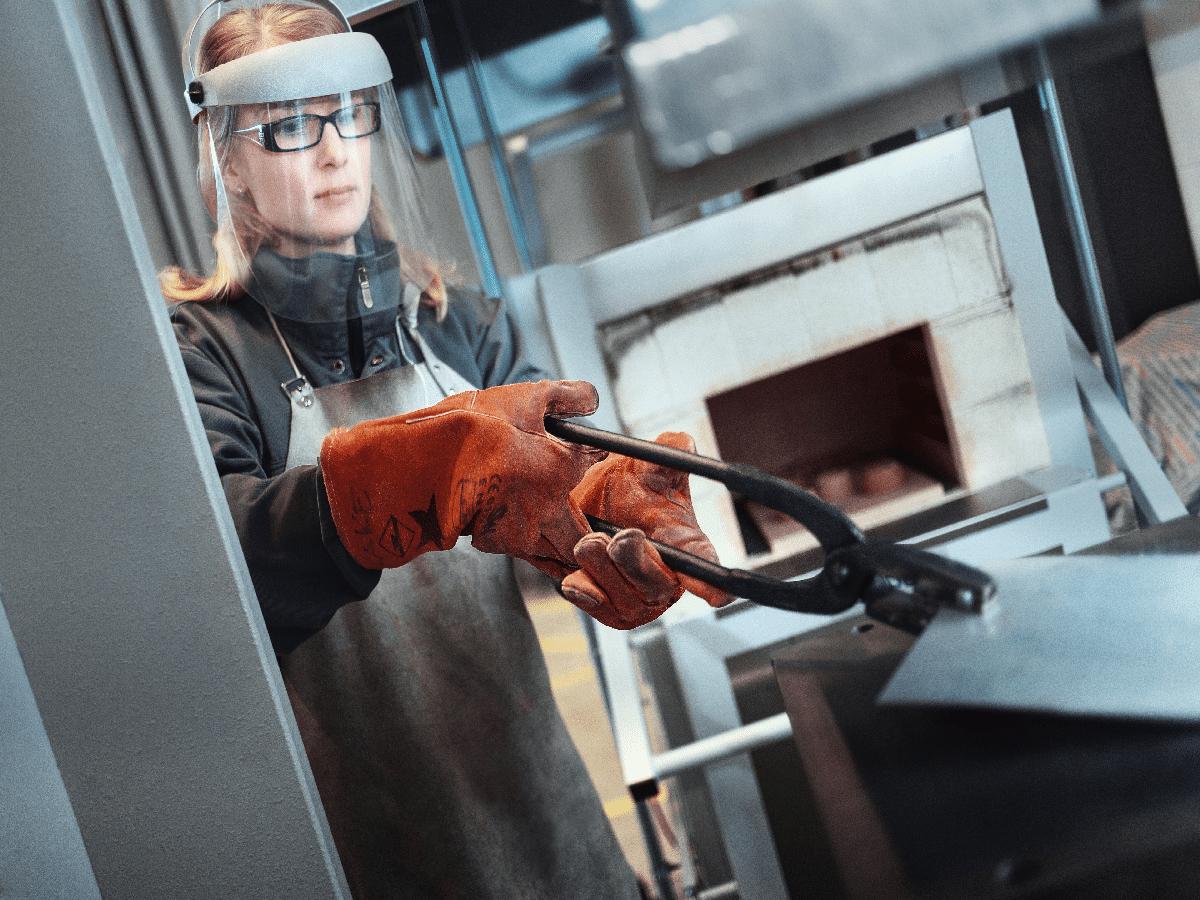 nainen pitetlee isoilla pihdeilla metallin palaa