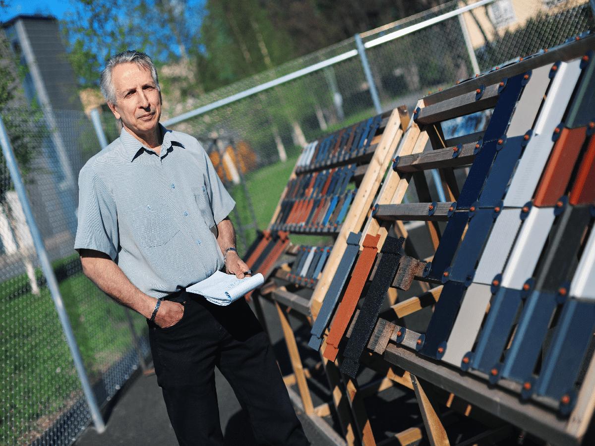 mies seisoo kattomateriaalien vieressa