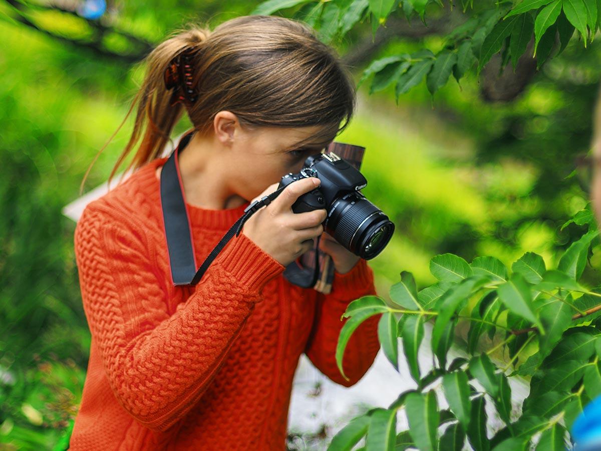 Nainen ottaa kameralla puusta lahikuvaa.