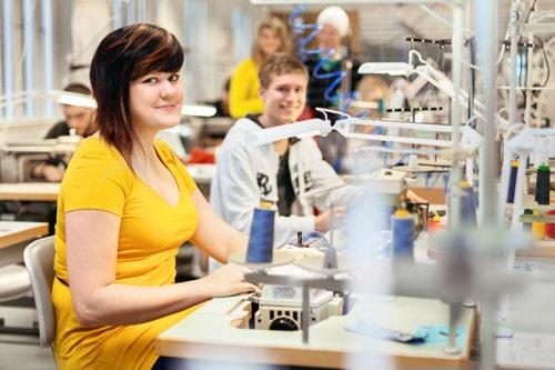opiskelijoita ompelukoneilla