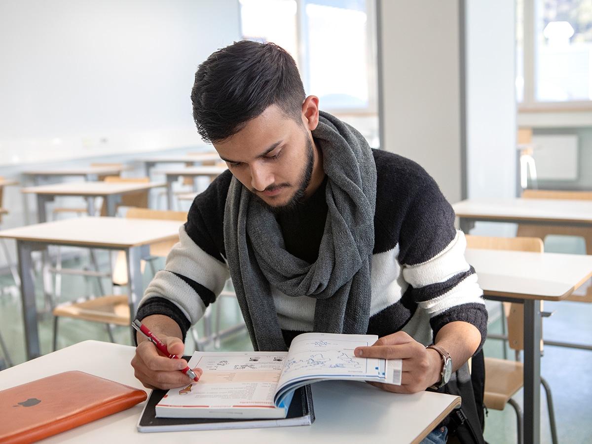 opiskelija kirjan ääressä