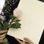 henkilö pitää ruusua ja todistusta