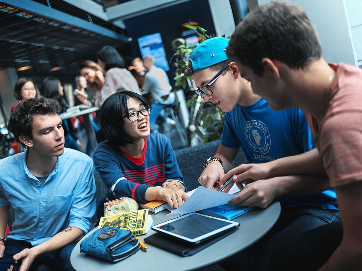 Opiskelijat työskentelevät pöydän äärellä