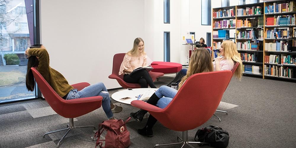 Ihmisiä istumassa kirjastossa