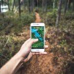 Kännykkä kädessä metsässä