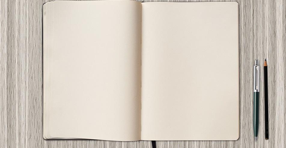 Tyhjä kirjan sivu ja kaksi kynää