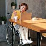 Nainen pyörätuolissa pöydän ääressä