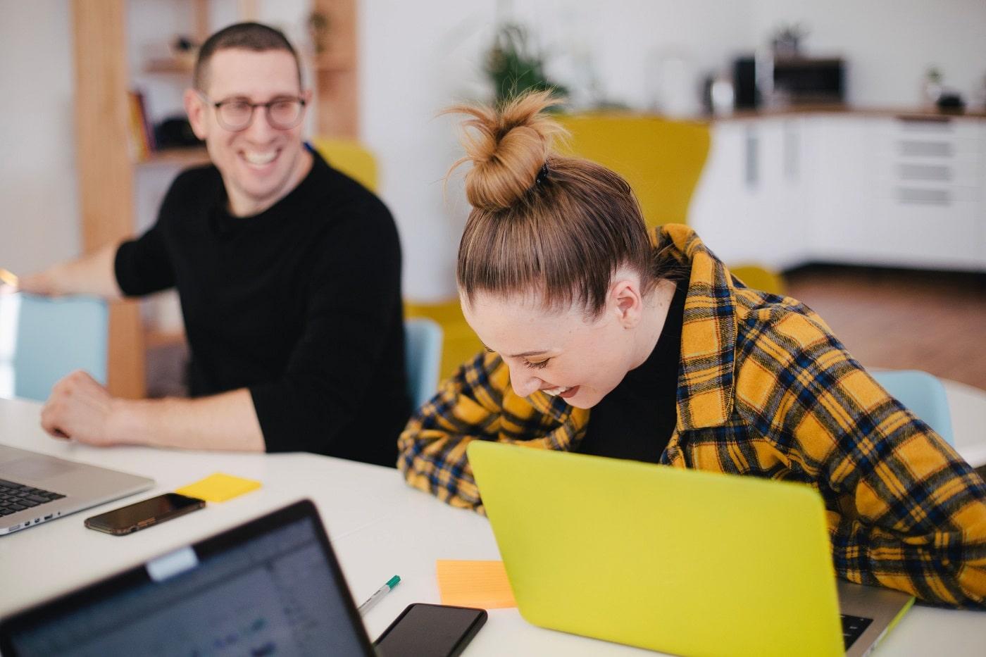 Nainen ja mies nauraa tietokoneen äärellä