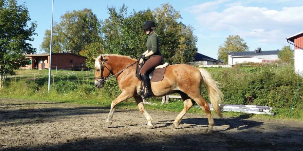 Nina Pyykönen ratsastamassa