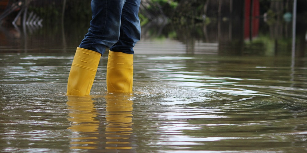 keltaisilla kumisaappailla tulvivassa lätäkössä