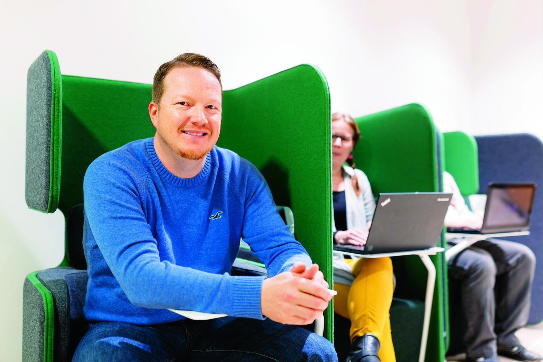 Aikuisia opiskelijoita vihreillä tuoleilla