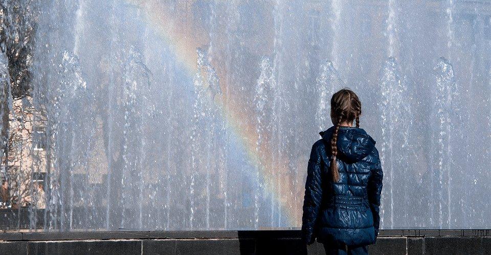 Tyttö selin katsomassa sateenkaarta