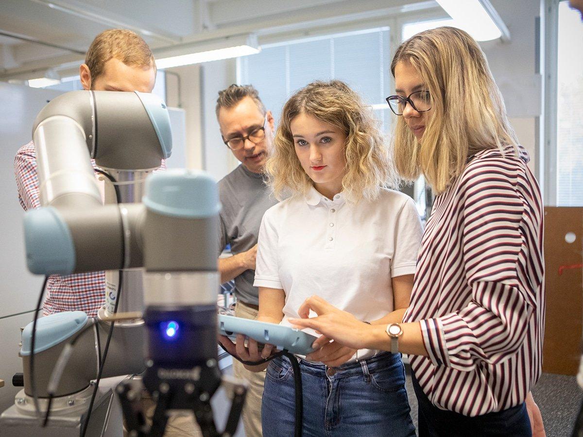 Opiskelijat työskentelevät laitteiston parissa