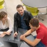 Opettaja ja kaksi opiskelijaa pöydän äärellä
