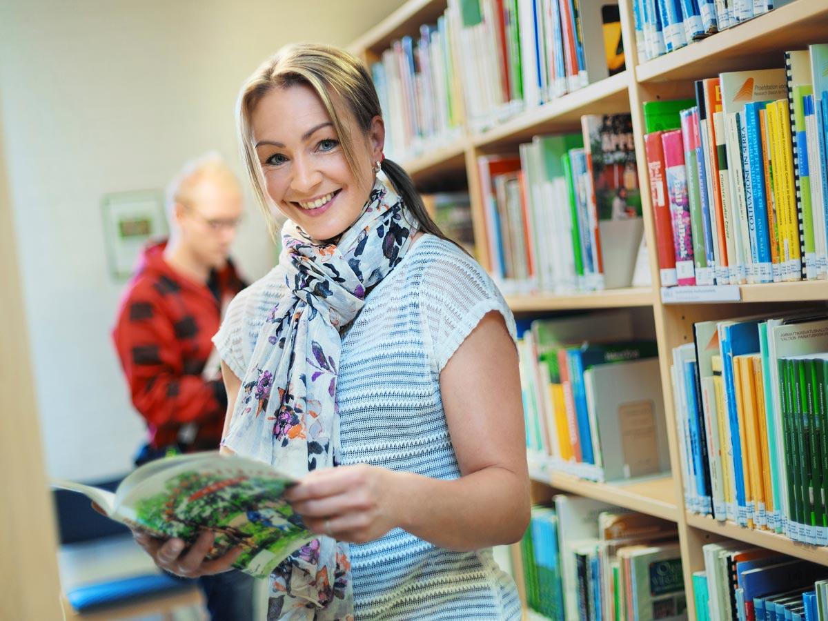 Nainen kirja kädessä HAMKin kirjastossa