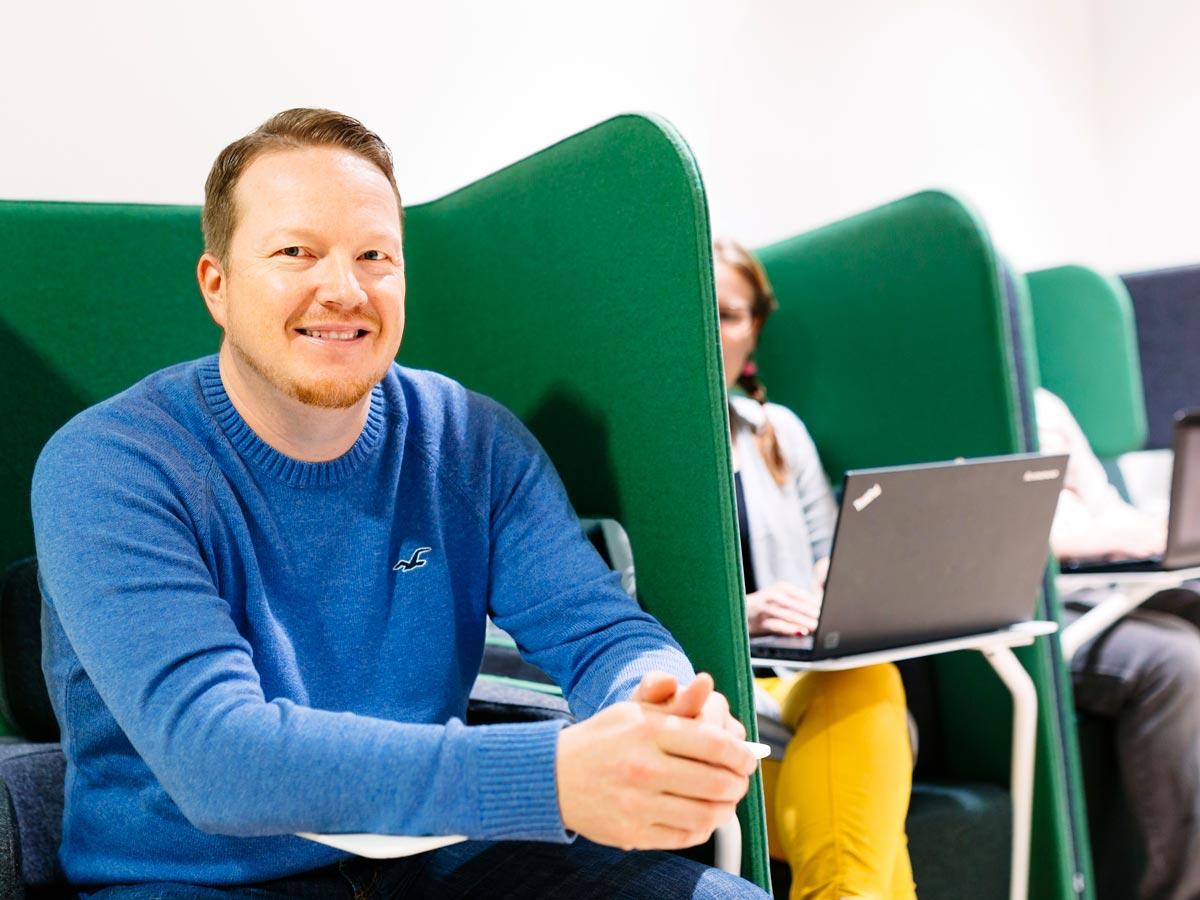 Mies hymyilee kameralle ja istuu vihreässä nojatuolissa