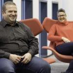 Mies ja nainen istumassa punaisilla nojatuoleilla