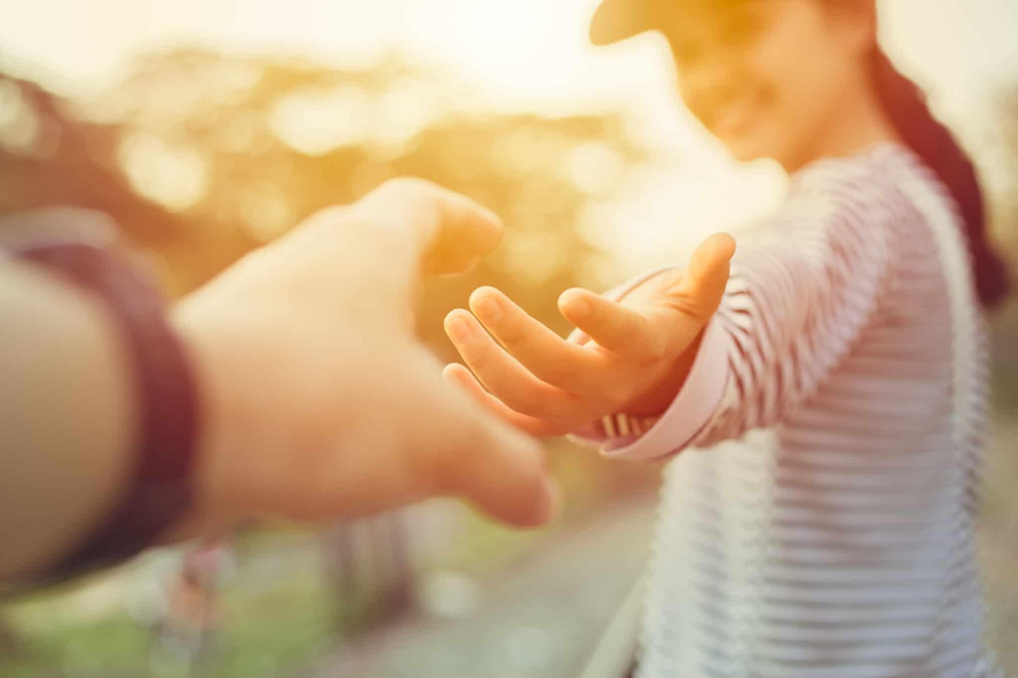 Henkilö tarttuu toisen henkilön käteen