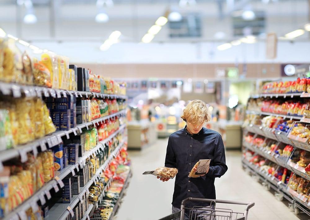 mies vertailee tuotteita kaupan käytävällä