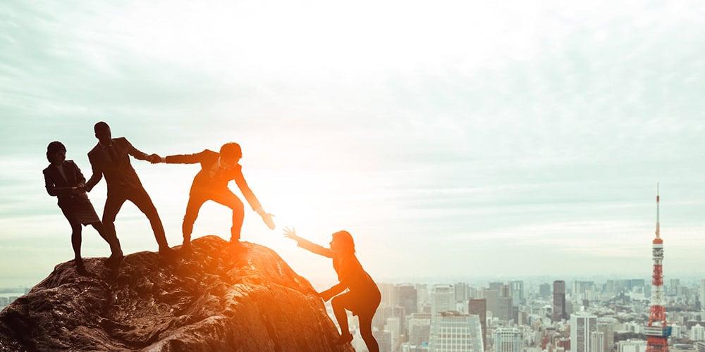 ryhmä ihmisiä auttaa neljättä ihmistä kiipeämään kallion päälle