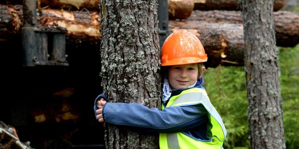 Lapsi turvavaatteissa halaa puuta
