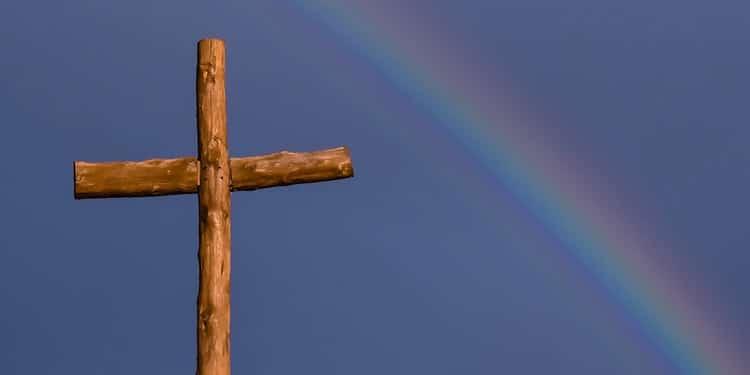 risti, joka taustalla on sateenkaari