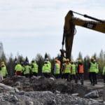 Työmaalla isoja kivilohkareita, opiskelijoita kävelemässä kaivurin vieressä