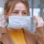 nainen asettaa maskia kasvoille