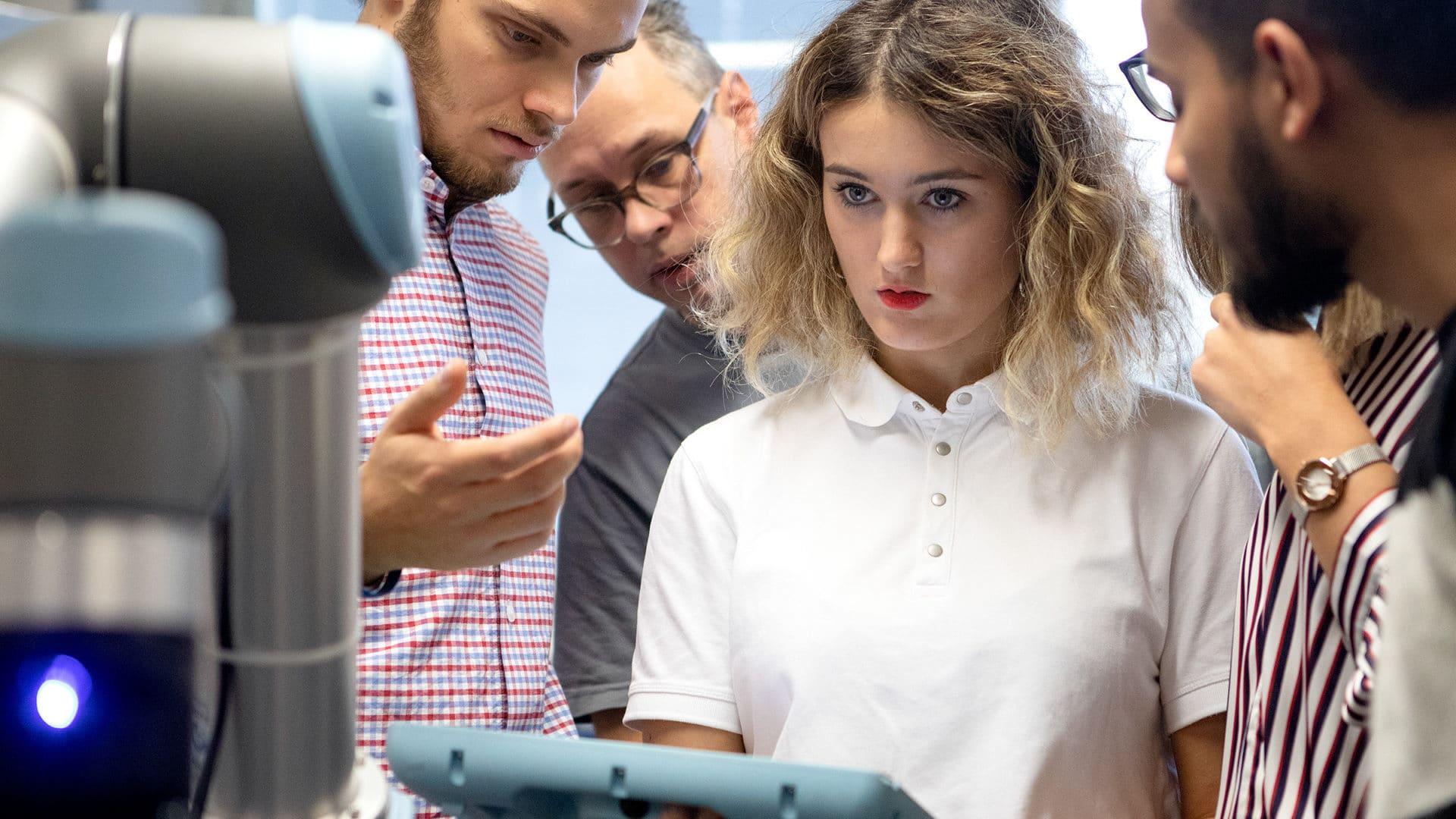 Insinööriopiskelija ohjaa robottia tabletilla.