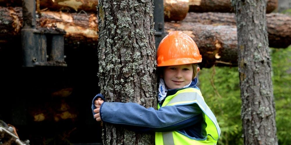 Puuta halaava lapsi kypärässä ja heijastinliiveissä