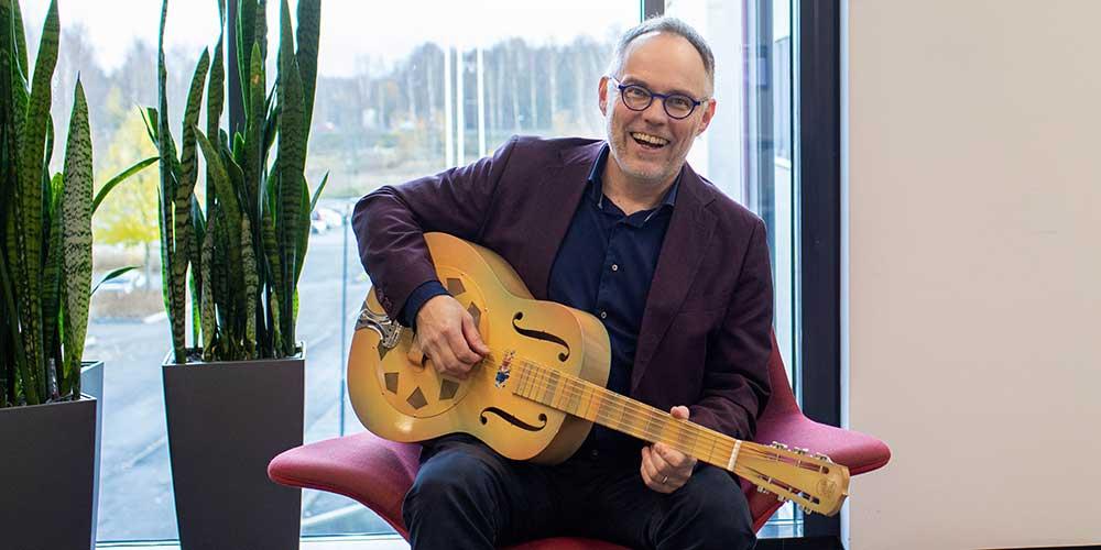Pertti Puusaari hymyilee ja soittaa kitaraa